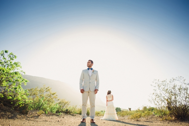 Groom portrait with bride in a desert.